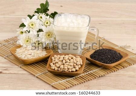 Soya milk and black sesame seeds on a white background. (Glycine max (L.) Merr.).  - stock photo
