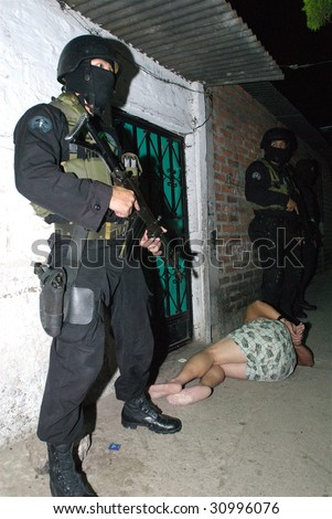 SOYAPANGO, EL SALVADOR, JAN 30: A Special Forces officer of the Grupo Reacion Policial (GRP) guards a gang suspect arrested at a raid against gang members on January 30, 2008 in El Salvador. - stock photo