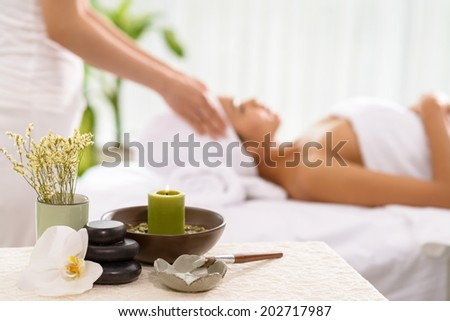 Spa accessories and a woman receiving spa treatment in the background - stock photo