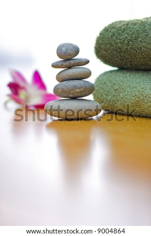 Spa and wellness: green towels and a stack of zen pebbles - stock photo