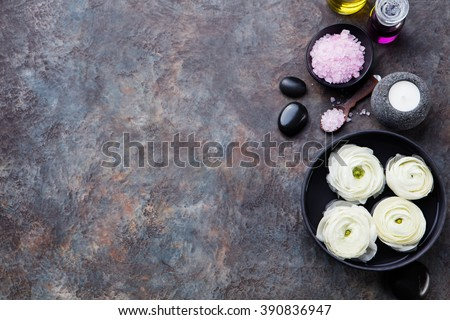 Spa and wellness massage setting, white floating ranunculus flowers Still life with essential oil, salt and stones Copy space Top view - stock photo