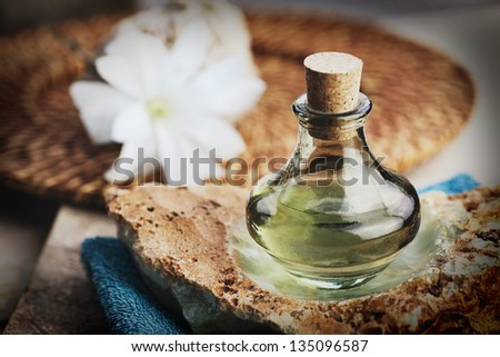 Spa and wellness setting with floral water, towel and flower - stock photo