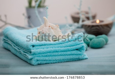 Spa and wellness setting with flowers, candles and towel. Blue dayspa nature set with copyspace - stock photo