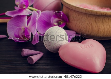 Spa and wellness setting with natural soap, sea salt and orchid. Spa treatment in purple, pink and violet colors with flowers on dark wooden background. Aromatherapy concept. Selective focus. - stock photo