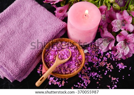 Spa and wellness setting with salt, candles and towel, petals - stock photo