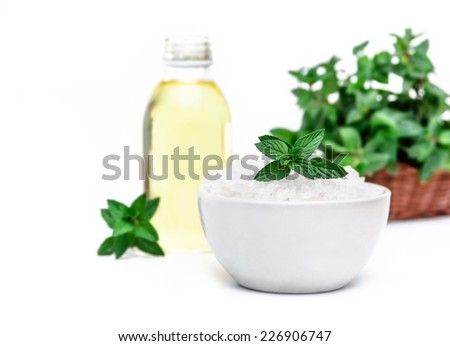 Spa and wellness setting with sea salt, oil essence and mint. Relax and treatment therapy. White background. Selective focus. Close up. - stock photo