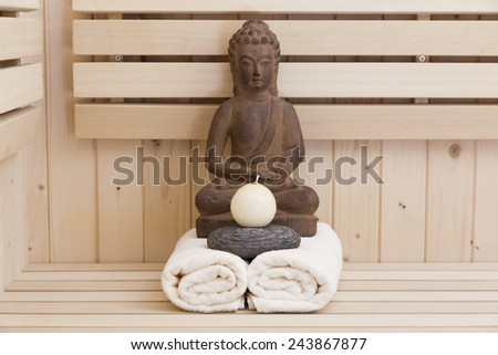 Spa and wellness setting with zen stone, buddha and towels - stock photo