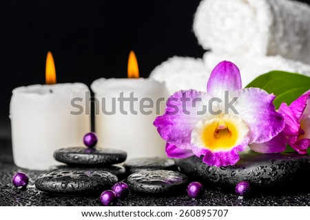 spa background of purple orchid dendrobium, leaf with dew, towels, white candles and pearl beads  on black zen stones - stock photo