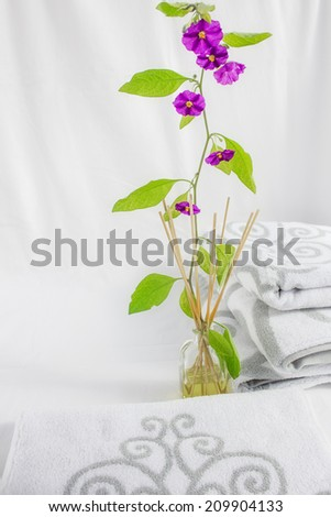 Spa background: pile of white towels and flower branch on a light background - stock photo