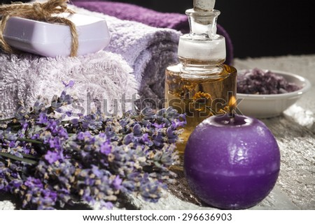 Spa background with bunch of lavender, towel, sea salt, candles and bottles with aromatherapy oil on a white wooden background. - stock photo