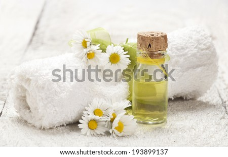 Spa background with glass vial with essential oil, rolled towel and chamomile on old wooden background. - stock photo