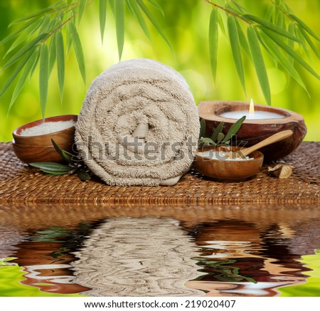 Spa background with rolled towel, bamboo and candlelight - stock photo