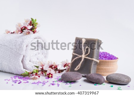 Spa bath cosmetic. Soap, flower branch beauty treatment background. Aromatherapy with natural salt and stones. Hygiene and relaxation for body. White towel. Luxury therapy and care. - stock photo