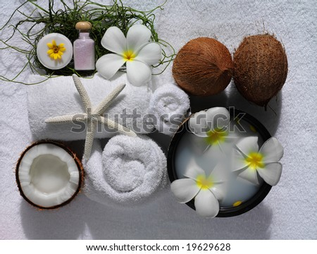 spa beauty objects with exotic flowers, coconuts, on white towels - stock photo