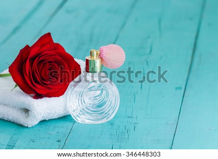 Spa composition of single red rose on white towel by perfume bottle with rustic antique teal blue wood background; Valentine's Day and love concept - stock photo