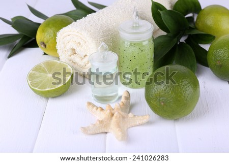 Spa composition with lime and towel color wooden background - stock photo