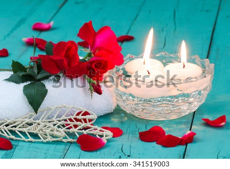 Spa composition with red flowers and rose petals, white towel, aroma bowl with three white floating candles on antique rustic teal blue wood background - stock photo