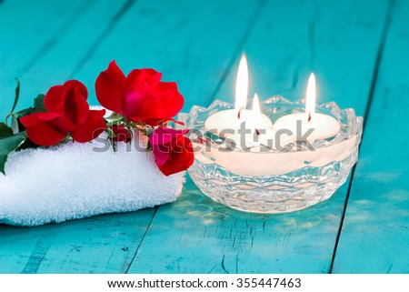 Spa composition with red flowers, white towel, aroma bowl with three white floating candles on antique rustic teal blue wood background - stock photo