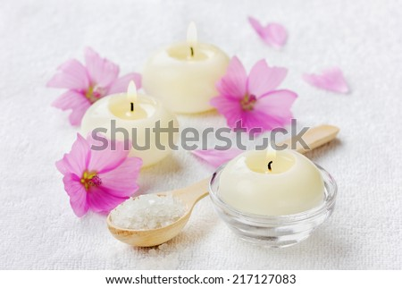 spa composition with sea salt bath in wooden spoon, pink flowers and burning candles on a white surface, aromatherapy concept - stock photo