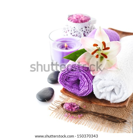 Spa composition with towels, massage stones, sea salt and lily flower - stock photo