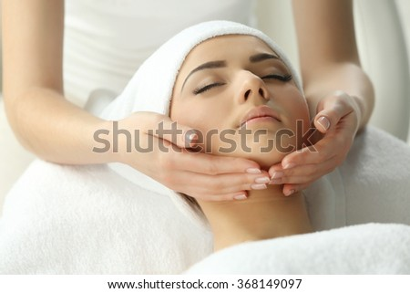 Spa concept. Face massage. Young woman getting spa treatment, close up - stock photo