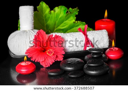 spa concept of red hibiscus flower with dew, candles, leaf, thai herbal compress ball and rolled towel on zen stones, closeup - stock photo