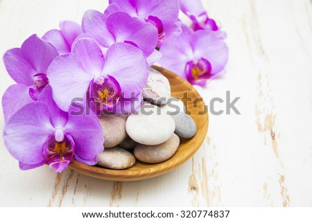 Spa concept of stones with drops in wooden plate, blooming twig stripped violet orchid - stock photo
