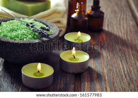 Spa concept. Sea salt in stone bowl with candle and herbal soap - stock photo