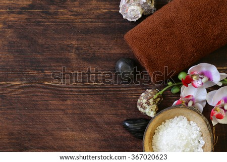 spa concept - towel, salt and orchid on wooden background - stock photo