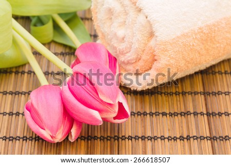 Spa concept: tulips with striped towel on bamboo-rug with place for text - stock photo