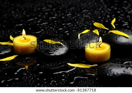 Spa concept-two candle with yellow flower petals on pebbles - stock photo