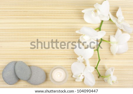 SPA concept: white orchids, candles and stones on mat. - stock photo