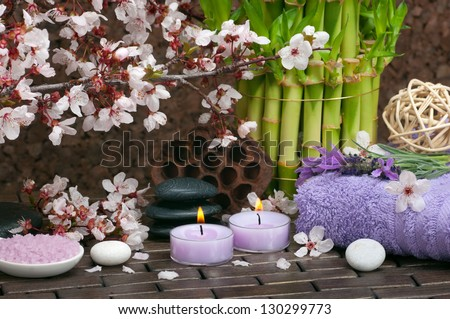 Spa concept with aromatic candles, lavender, bath salts, healing pebbles, cotton towels - stock photo