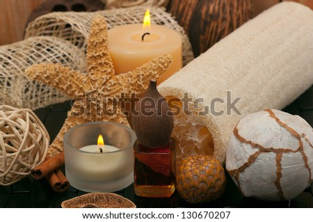 Spa concept  with aromatic candles, massage oil and loofah - stock photo