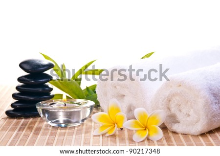 Spa concept with black zen stones, flowers on bamboo mat background - stock photo
