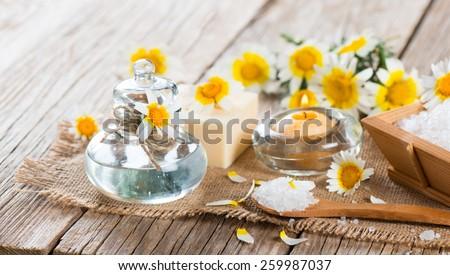 Spa concept with chamomile flowers, white salt and candle on a old wooden background - stock photo