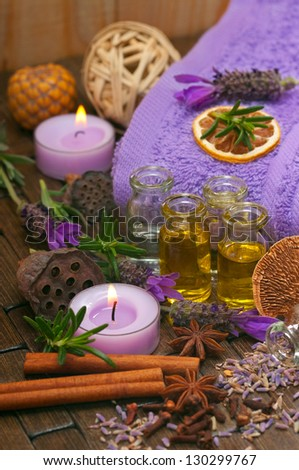 Spa concept with massage oils, aromatic lavender, spices, candles and cotton towels - stock photo