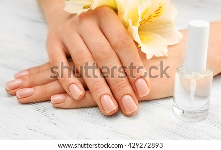 Spa concept. Woman hands with beautiful flowers and nail polish on wooden background, close up - stock photo