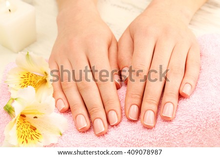 Spa concept. Woman hands with beautiful manicure and flowers on towel, close up - stock photo