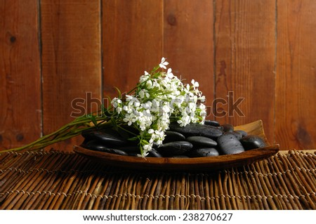 spa concept zen basalt stones in bowl mat with branch of tropical flower - stock photo
