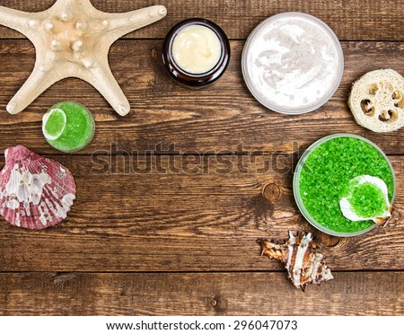 Spa cosmetics and accessories: sea salt, loofah, skin care cream, natural scrubs with shells and starfish on wooden planks. Top view. Frame, copy space - stock photo