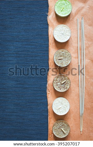 SPA dark blue background for text with aroma candles, incense sticks and orange ornamental paper. Top view. Low contrast toned - stock photo