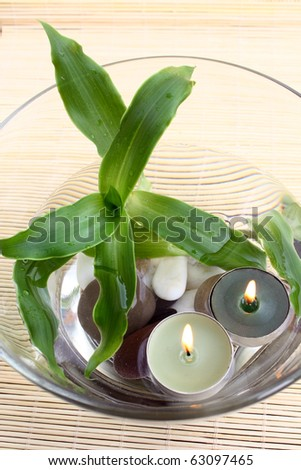 spa decoration: top view of bowl with water, pebbles, plant and burning candles - stock photo