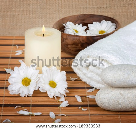 Spa decoration with candle, daisies and spa stones - stock photo
