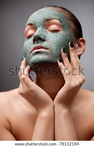 Spa dreams. A portrait of a beautiful relaxing lady  with a clay mask on her face. - stock photo