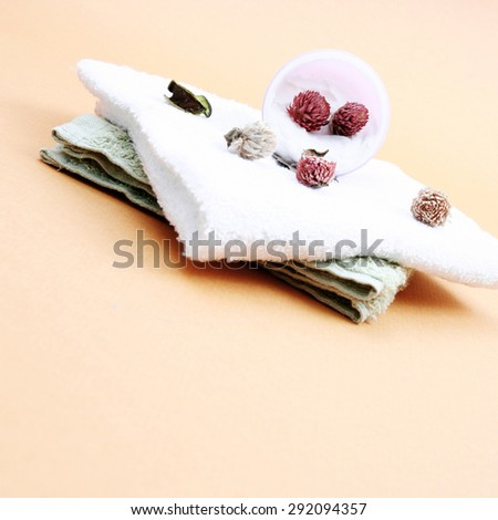 Spa essentials (cream, white towel and pink flowers) isolated on yellow - stock photo