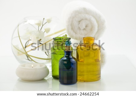 Spa feeling (flower, towel, candle and bottles of essential oil). - stock photo