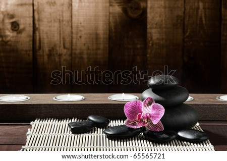 spa frame from bamboo grove, pink orchid and black zen stones on the old wooden background - stock photo