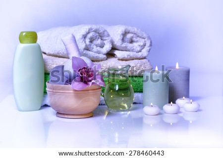 spa items with lilac orchid on blue background - stock photo