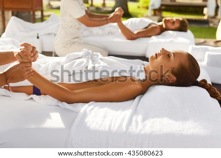 Spa Massage. Beautiful Couple Relaxing At Relax Beauty Centre, Man And Woman Enjoying Hand Massage Outdoors. Masseur Massaging Hands With Aromatherapy Oil. Body Skin Care, Summer Relaxation Concept - stock photo